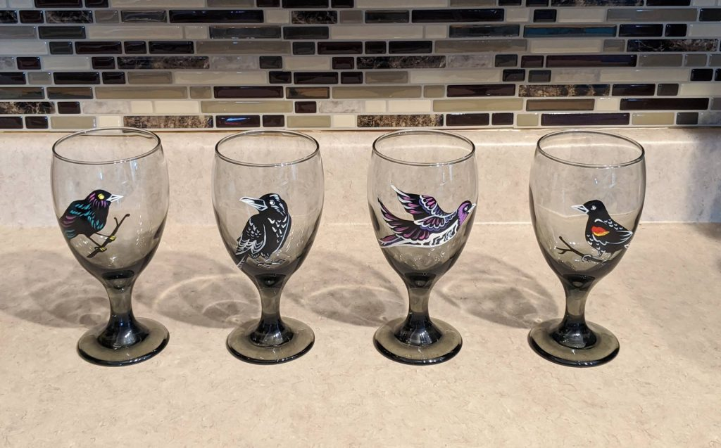 $35.00, Set of 4 Hand Painted Goblets - Featuring a blackbird, raven, amethyst starling, and red winged blackbird. Paint is cured and baked to a permanent finish - wash safe! Artist: Allise Noble